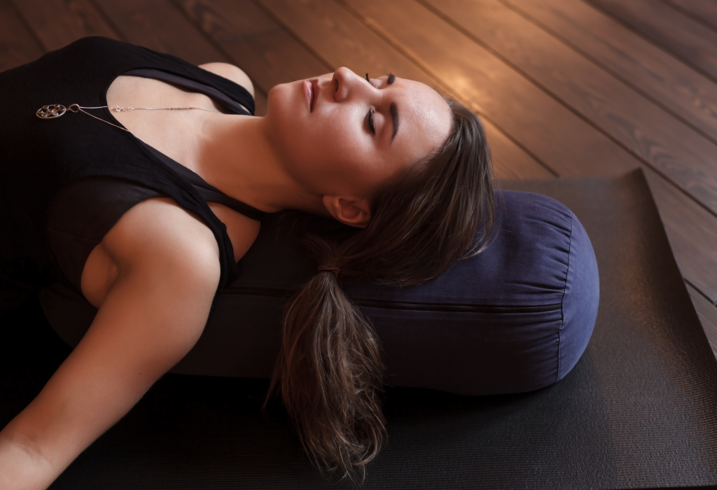 Woman relaxed in a yoga therapy posture supported by pillows